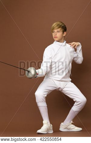 Boy Fencer Standing In Attacking Pose. Portrait Of Teenage Boy Wearing White Fencing Suit Posing Wit