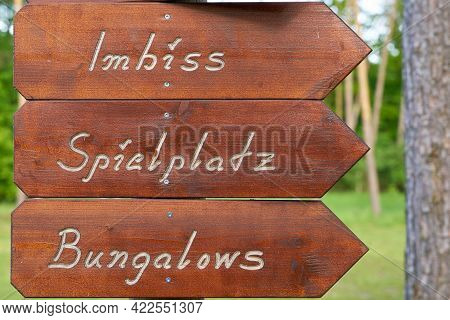 Signpost On A Campsite In Germany With The Inscription Snack Bar, Playground, Bungalows (imbiss, Spi