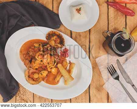 Peruvian Food: Peruvian Dish A Lo Macho Fish, Wooden Table, Served On A White Plate, (fish Fried In