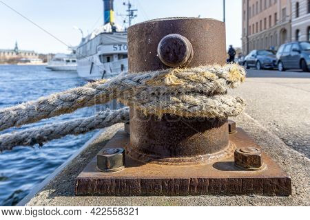 Stockholm, Sweden - April 17, 2021: Mooring Rope Around Rusted Bollard In The Middle Of Stockholm An