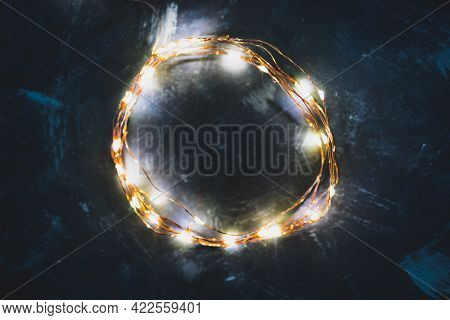 Fairy Lights Arranged In A Circle Shining Over Blue Background With Copy Space To Add Text
