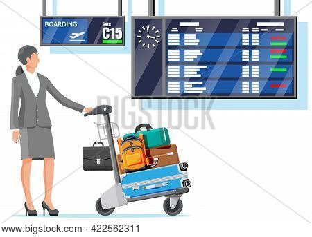 Woman And Hand Truck Full Of Bags In Terminal. Departure Arrival Timetable. Airport Luggage Trolley.