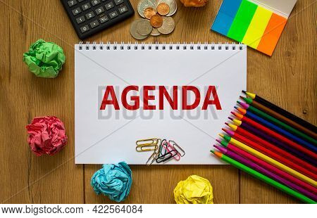 Agenda Symbol. White Note With The Concept Word 'agenda' On Beautiful Wooden Table, Colored Paper, C