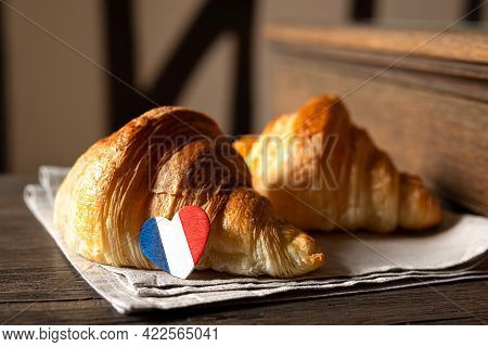 Two Fresh French Croissants And A Heart In The Colors Of The French Flag On A Table