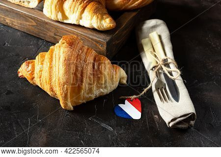 Fresh French Croissants In A Wooden Tray, Cutlery And A Heart In The Colors Of The French Flag On A