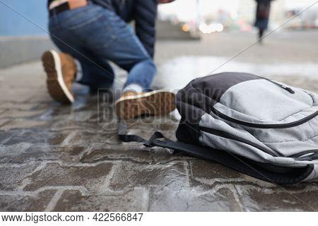 Man With Backpack Felling On Slippery Sidewalk In Winter Closeup