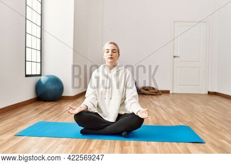 Young blonde girl concentrated doing yoga at sport center.