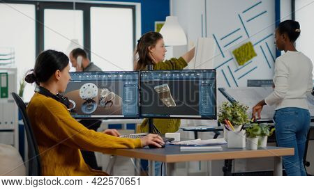 Industrial Female Engineer Looking At Personal Computer With Dual Monitors Setup, Screens Showing Ca