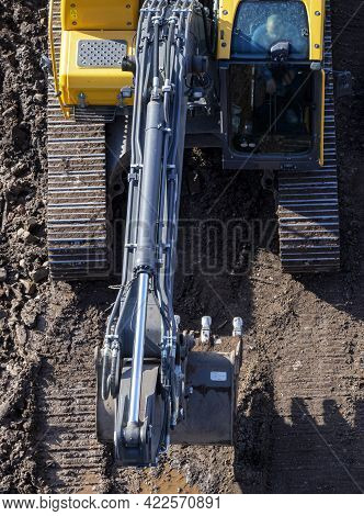The Excavator Drives On The Ground, Leaving A Tracked Track. View From Above. The Front Of The Excav