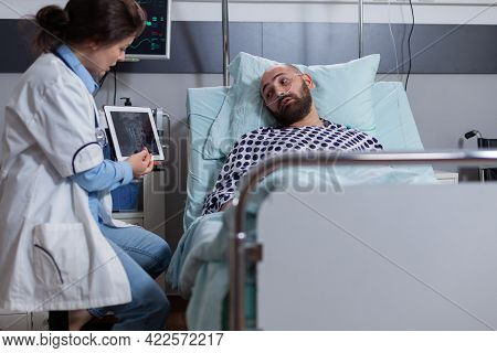 Physician Doctor Woman In Medical Uniform Explaining Bones Radiography To Sick Man During Recovery E