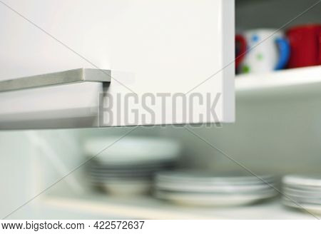 Closeup Of An Opened Grey Kitchen Cabinet Door With Metal Handle And Plates And Mugs Inside.