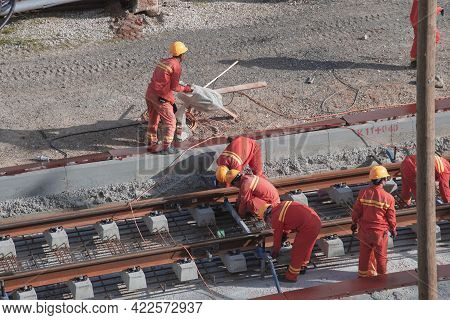 Tel Aviv, Israel - May 20 2021: Construction Workers With Orange Overalls. Light Rail Tracks. Blue C