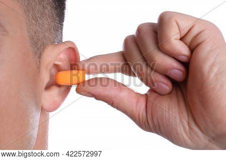 Man Inserting Foam Ear Plug On White Background, Closeup