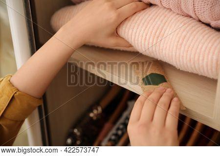 Woman Putting Scented Sachet In Wardrobe, Closeup