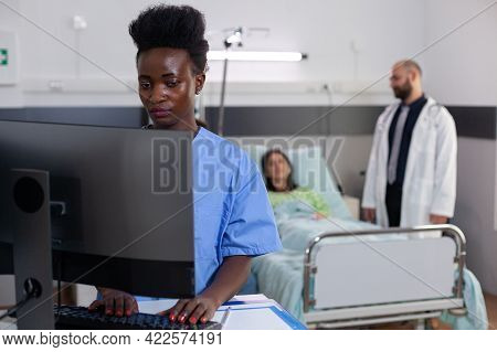 Afro American Nurse Typing Disease Symptom While Specialist Practitioner Doctors Monitoring Sick Wom