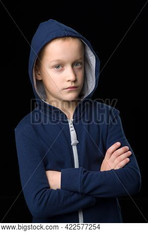 Portrait Of Cool Boy In Blue Hoodie. Stylish Preteen Boy Looking Seriously At Camera Against Black B
