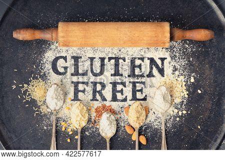 Gluten free written in flour on vintage baking sheet, rolling pin and spoons of various gluten free flour (almond, buckwheat, rice, corn, oatmeal), gluten free baking concept