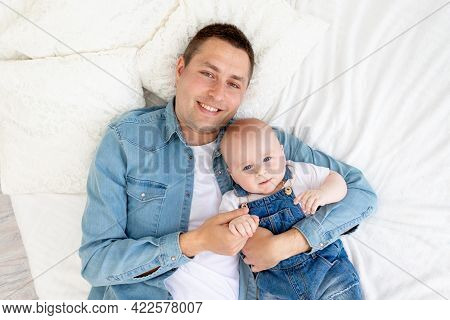 Happy Father With Baby Son Lying On The Bed And Cuddling Having Fun, The Concept Of Father's Day Or