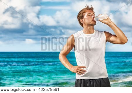 Sports drink fitness man drinking water botlle during outdoor exercise workout on beach. Dehydrated athlete runner after run sweating in summer heat exercising cardio.