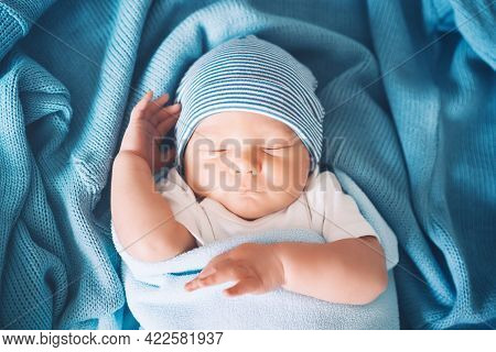 Newborn Sleep At First Days Of Life. Portrait Of New Born Baby One Week Old In Crib In Cloth Backgro