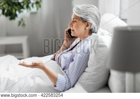 old age, technology and people concept - senior woman in pajamas calling on smartphone sitting in bed at home bedroom