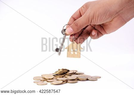 Hand Holding House Key On Money Coin Stack And White Isolated Background.