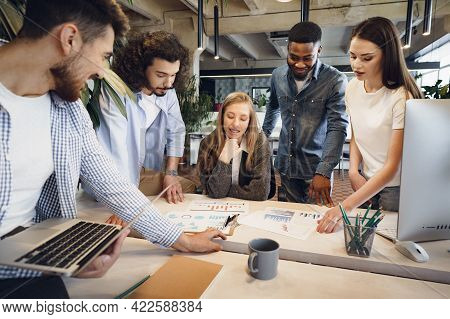 Team Of Diverse Coworkers In Modern Office Discuss Their Project Together