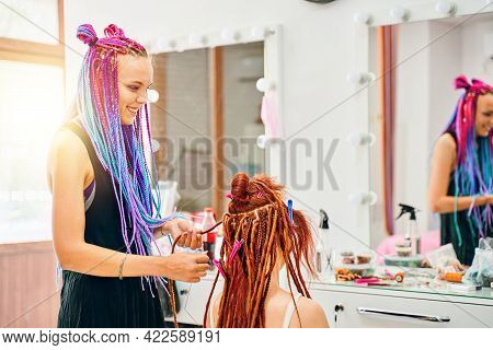 Woman Hairdresser With Colored Afro Braids Weaves To Girl Ginger Dreadlocks. Hippie Style Hair. Weav