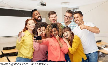 diversity, education and school concept - group of smiling international university students and teacher taking selfie with smartphone over lecture hall on background