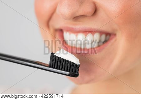 A Woman With A Snow-white Smile Holds A Toothbrush With Paste On A White Background