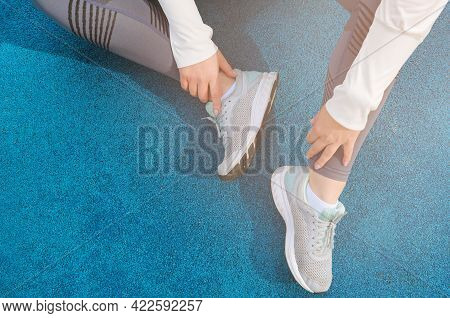 Legs Of A Woman In Gray Leggings And Gray Sneakers, On A Blue Coating Top View