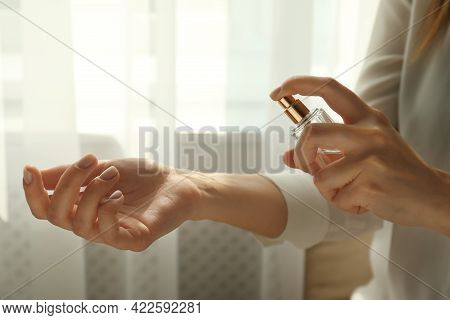 Woman Applying Perfume On Wrist Indoors, Closeup