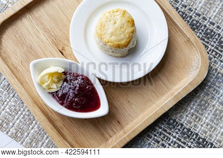 Scones And Strawberry Jam Cups On Wooden Trays On Tables At The Café