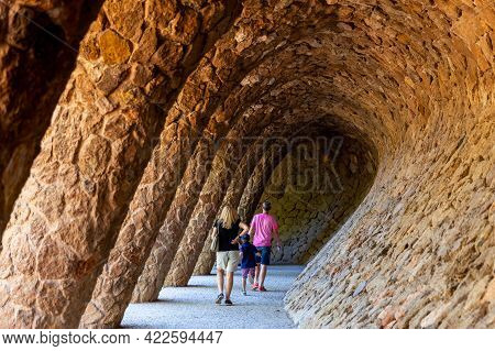 Barcelona, Spain - October 5, 2018: Tourist Family Walking On Colonnaded Pathway Under Hill Of Park