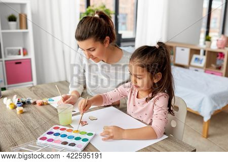 family, motherhood and leisure concept - mother spending time with her little daughter with colors painting chipboard items at home