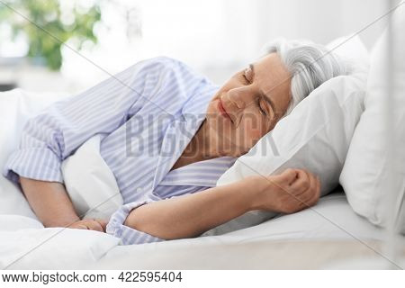 old age and people concept - senior woman sleeping in bed at home bedroom