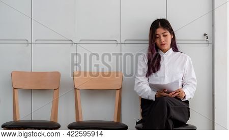 Asian Woman With Resume Sitting To Review The Documents While Waiting For A Job Interview