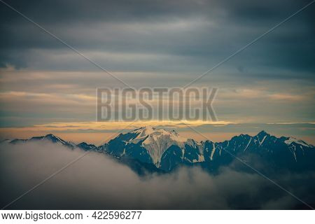 Atmospheric Dawn Mountain Landscape With Great Snowy Mountain Peak In Sunlight Above Big Low Cloud A