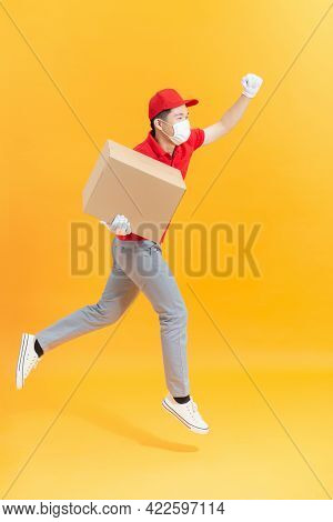 Fun Jumping Delivery Man In Red Cap T-shirt Uniform Sterile Face Mask Gloves Isolated On Yellow Back
