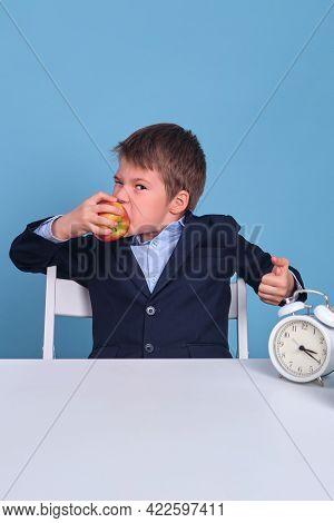 Junior In School Uniform Eats An Apple At His Desk, Blue Background