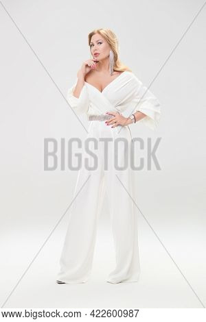 Fashion shot. Full length portrait of a glamorous middle-aged woman in a chic suit and jewelry posing at studio on a white background. Luxury lifestyle.