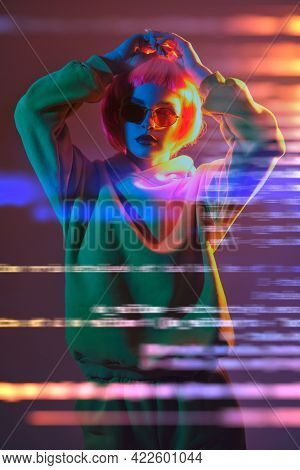 Modern girl with bright pink hair poses in red sunglasses and yellow suit in mixed color light. Sport chic fashion. Youth fashion and beauty trends.