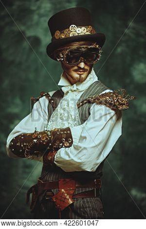 Portrait of a handsome victorian steampunk man on a grunge background. Fantasy world, scientific inventions.