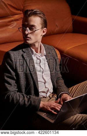Well-groomed young man in elegant clothes and glasses sits by a leather sofa with laptop in a modern luxurious apartment. Business style, businessman.