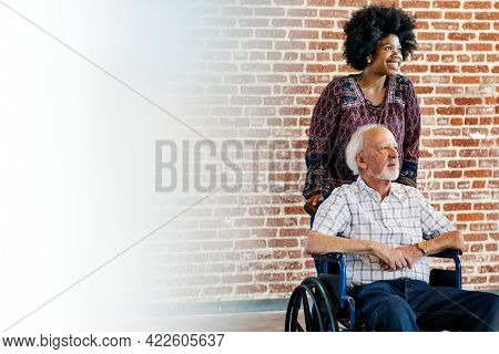 Black woman pushing her patient's wheelchair