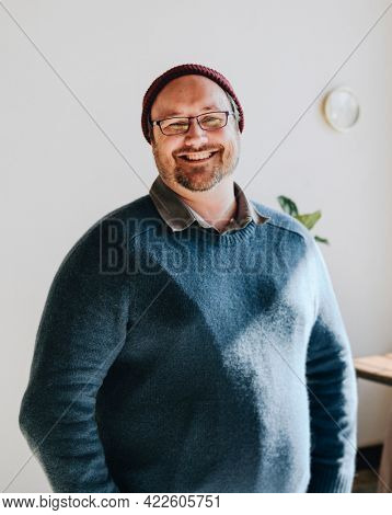 Cheerful man in a blue sweater and a red knitted hat