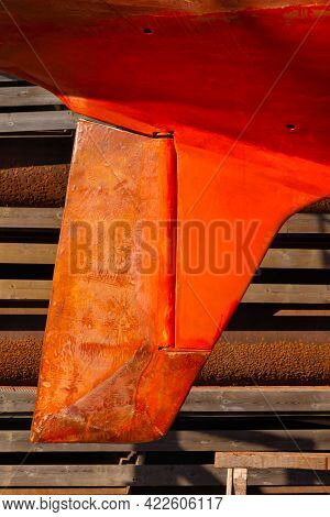 Rudder Blade Wooden Yacht Covered With Primer And Orange Paint In Dry Dock. Service, Maintenance And