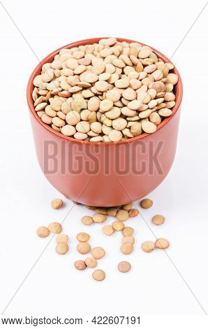 Brown Lentils In Cup On White Background.