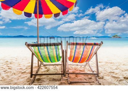 Two Colorful Beach Chair With Umbrella On The Beach