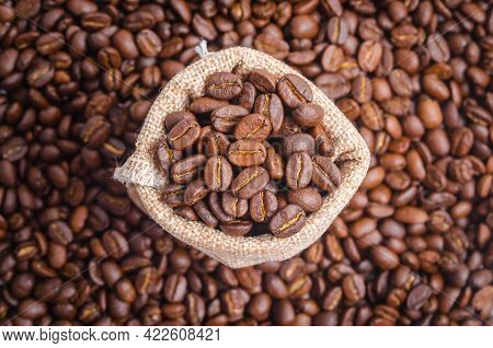 Coffee Beans In Sack Bag On Coffee Beans Background.